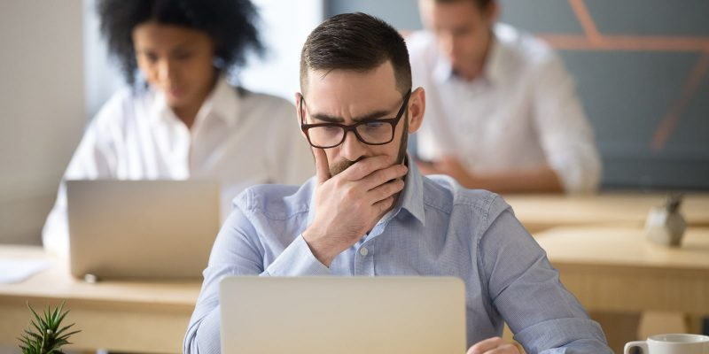 Man looking worried with computer in office