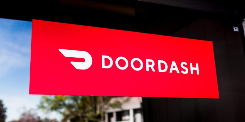 DoorDash logo and text on red sign with a black and blue background