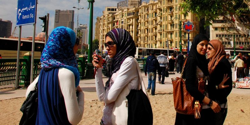 Modern young Egyptian women talk on a street in Cairo