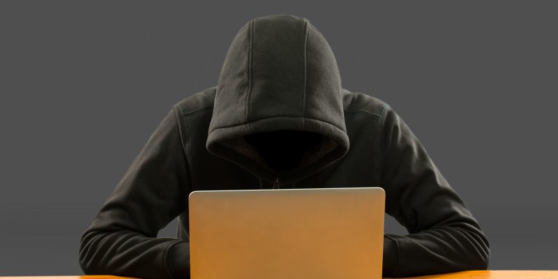Cloaked figure using a laptop
