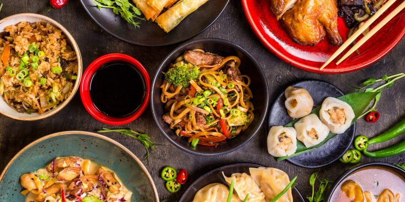 Noodles, dumplings, dim sum, spring rolls and other famous Asian dishes on table