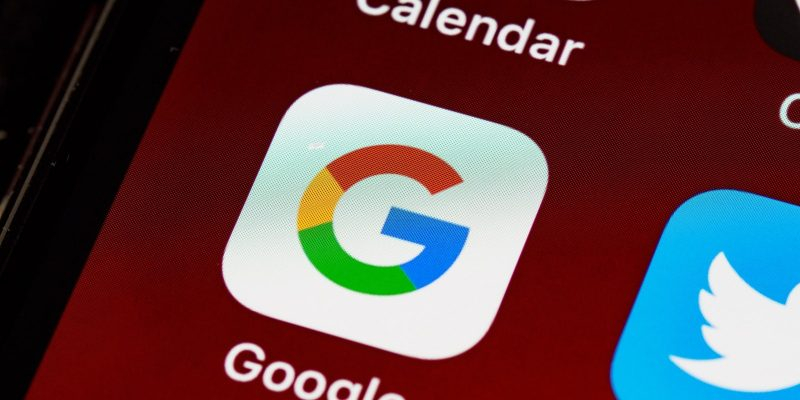 Close up of Google App Icon on a red background on a smartphone