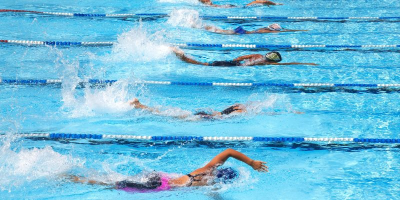 Swimmers Competing in Swimming Pool