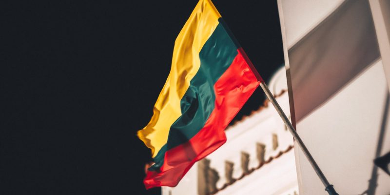 Lithuanian Flag on the side of a building on a black background