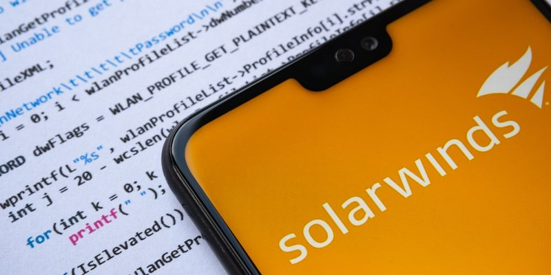 Solarwinds logo seen on the smartphone screen, with simple C attack code on the paper background