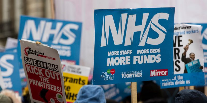 Protesters with signs at an NHS protest
