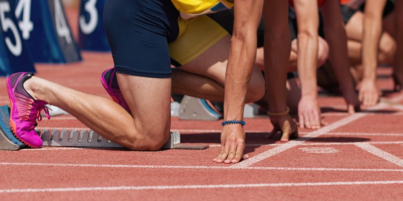 Group of male track athletes on starting blocks. Hands on the starting line. Athletes at the sprint start line in track and field.