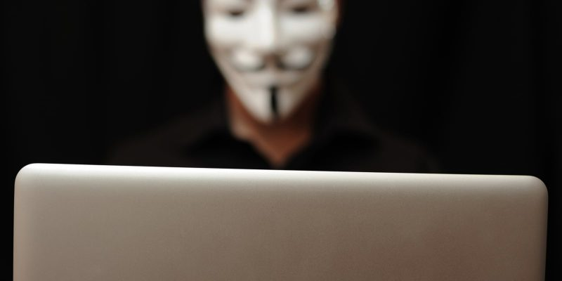 Person with a Guy Fawkes Mask with a Laptop in Focus on a Black Background
