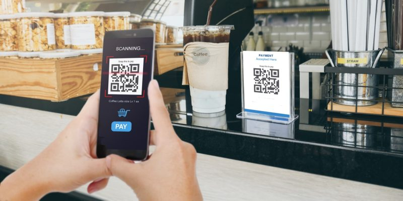 Person scanning QR code with his smartphone to make a payment