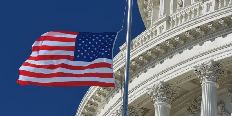 American flag flying outside the Capitol building