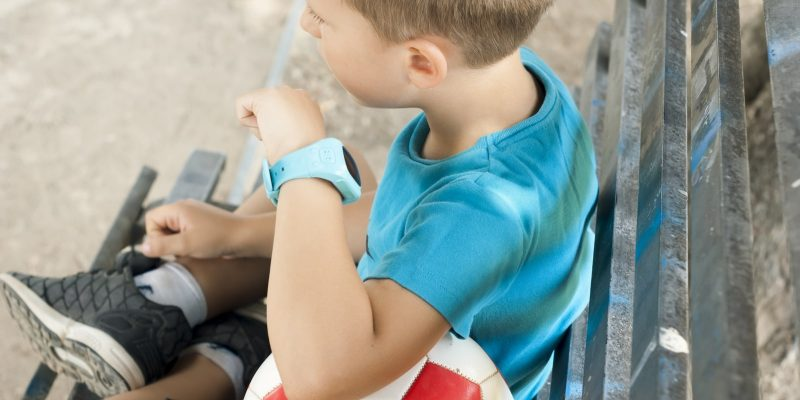 Child with smartwatch sitting on a bench