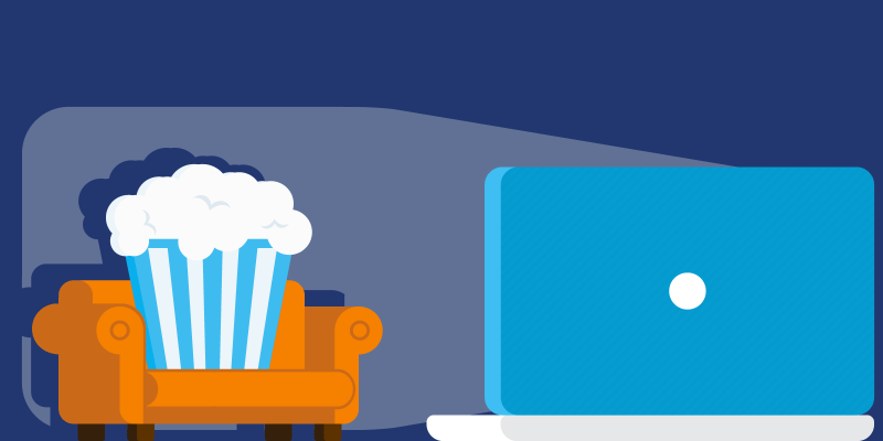 Bucket of popcorn on a couch watching a movie on a laptop