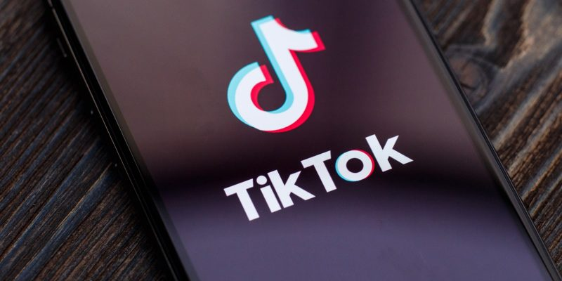 TikTok Logo on an iPhone X that is set on a wooden surface