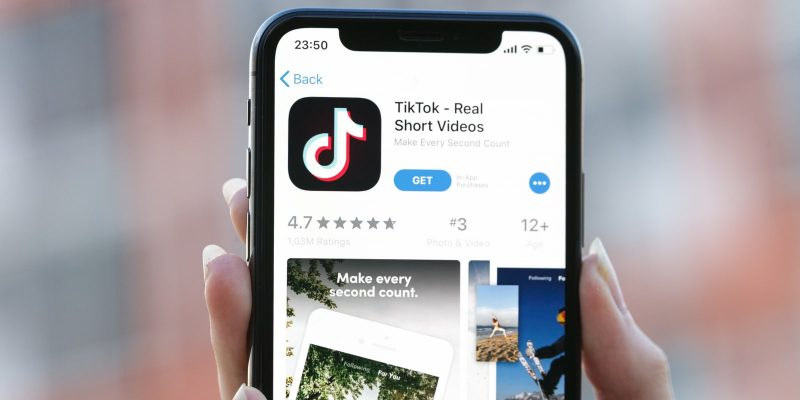 TikTok App on App Store on an iPhone held by a person