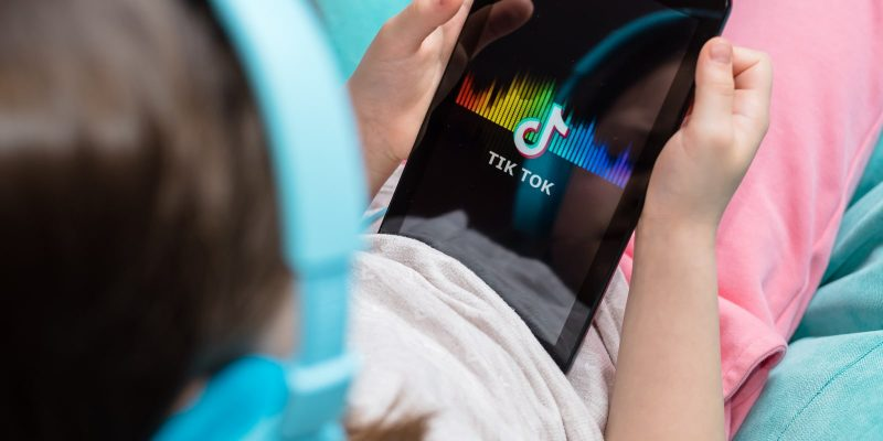 Tiktok Settles Dozens of Privacy Lawsuits - child holding tablet with TikTok icon on screen