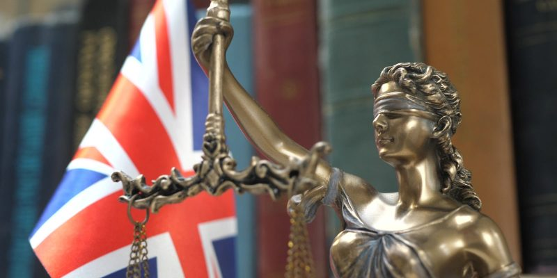 Lady justice infront of UK flag