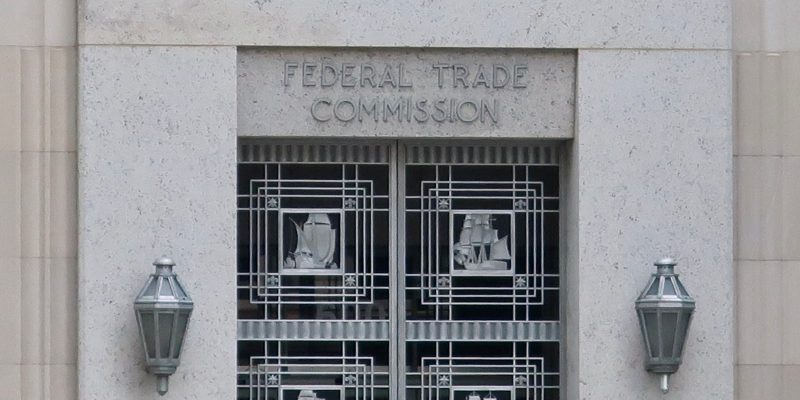 Building with the words Federal Trade Commission Above A Door With Wall Lamps on Either Side