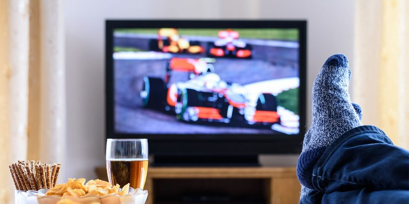 person watching Formula 1 on TV